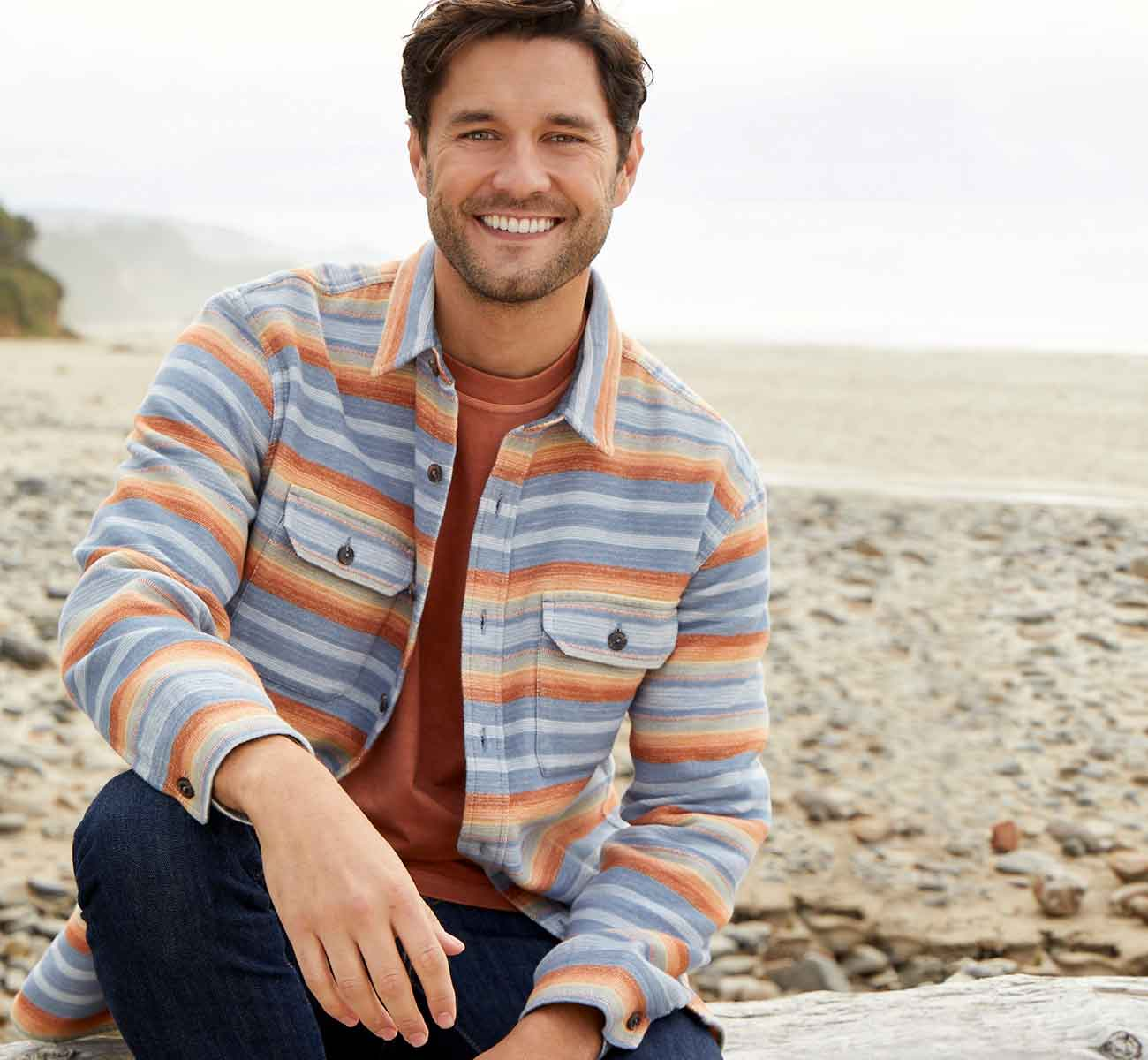 Male model seated on the beach in a striped button-up shirt