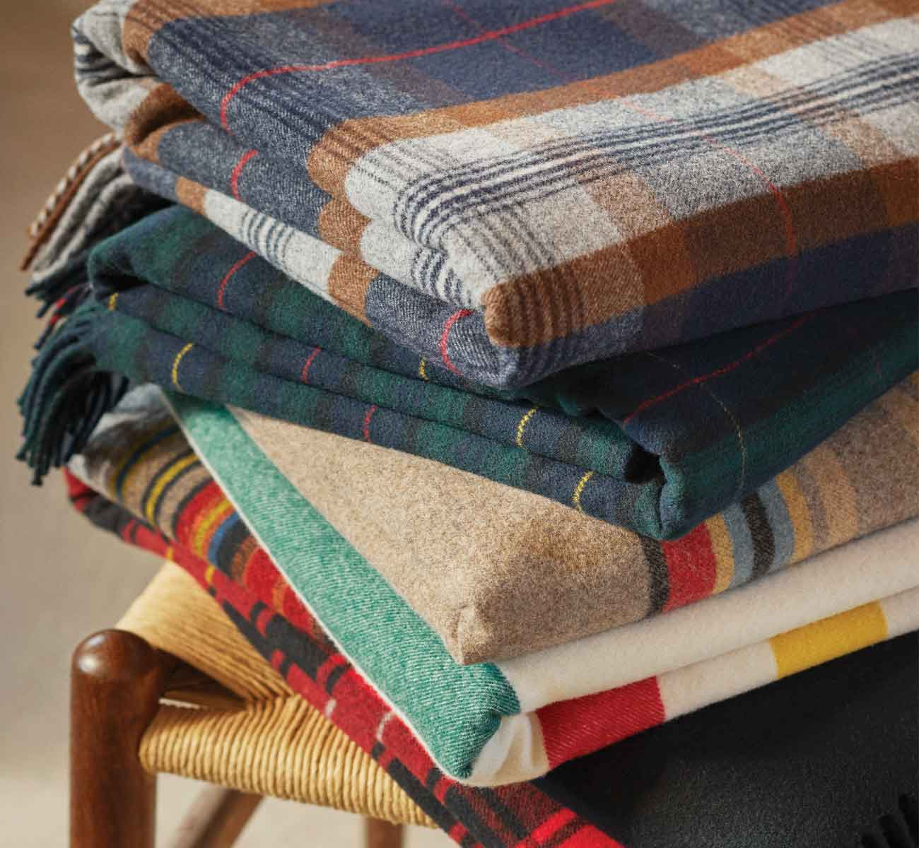 Stack of patterned blankets sitting on a chair