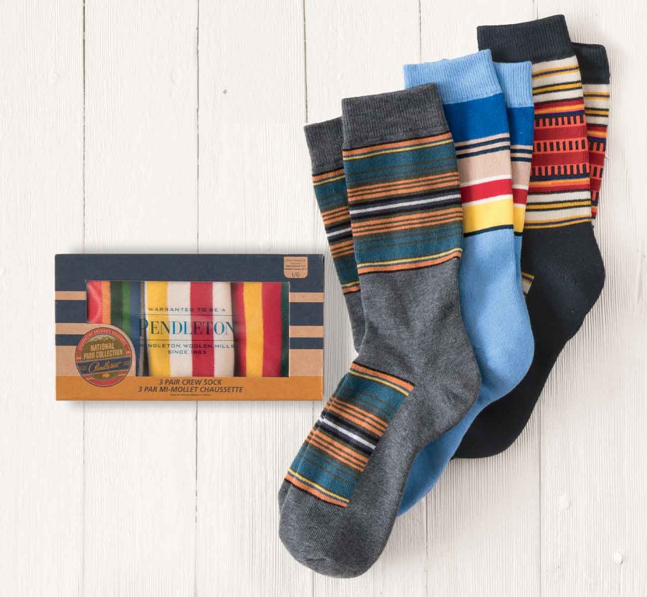 Three pairs of colorful striped socks next to a gift box