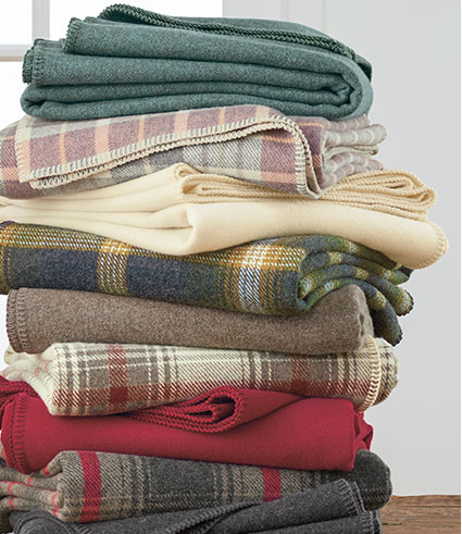 Stack of folded Eco-WIse plaid and solid wool blankets