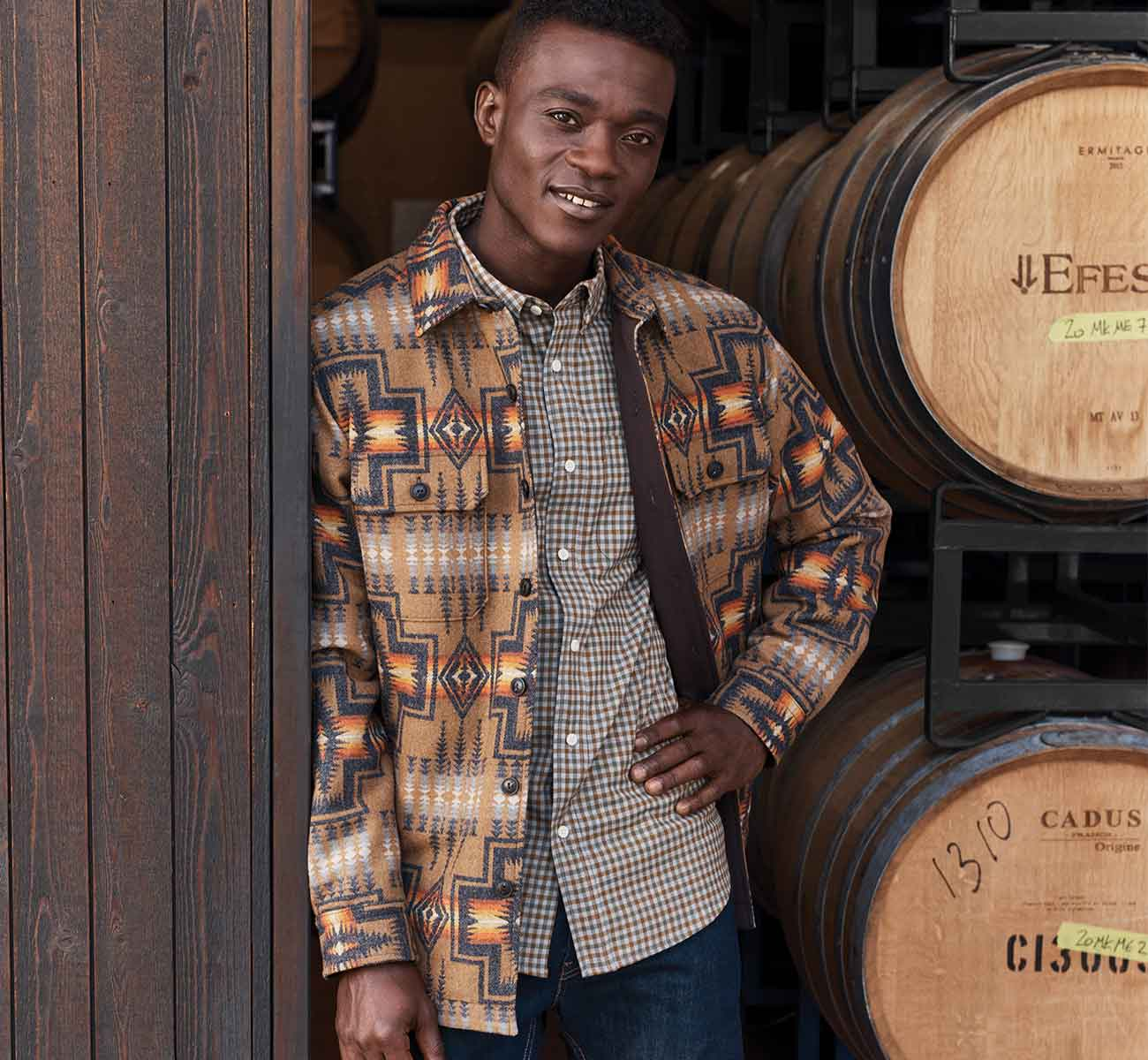 Man wearing a quilted shirt jacket standing in a barn door