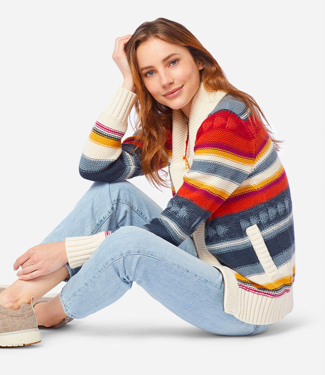 Seated woman wearing the Campfire Zip Cardigan sweater