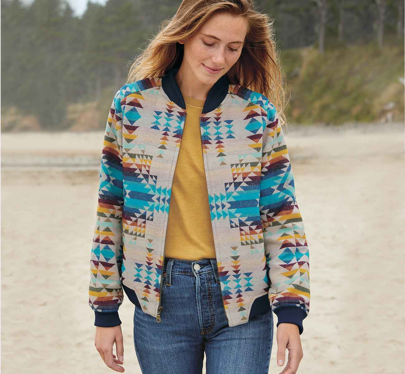 Woman walking on a beach in a brightly colored wool bomber jacket