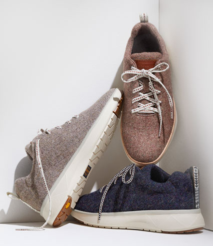 Three individual lace-up sneakers in grey, navy, and pink