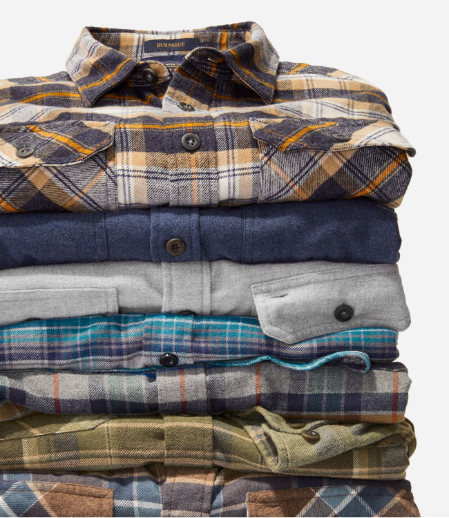Stack of folded men's cotton shirts in plaid and solid colors