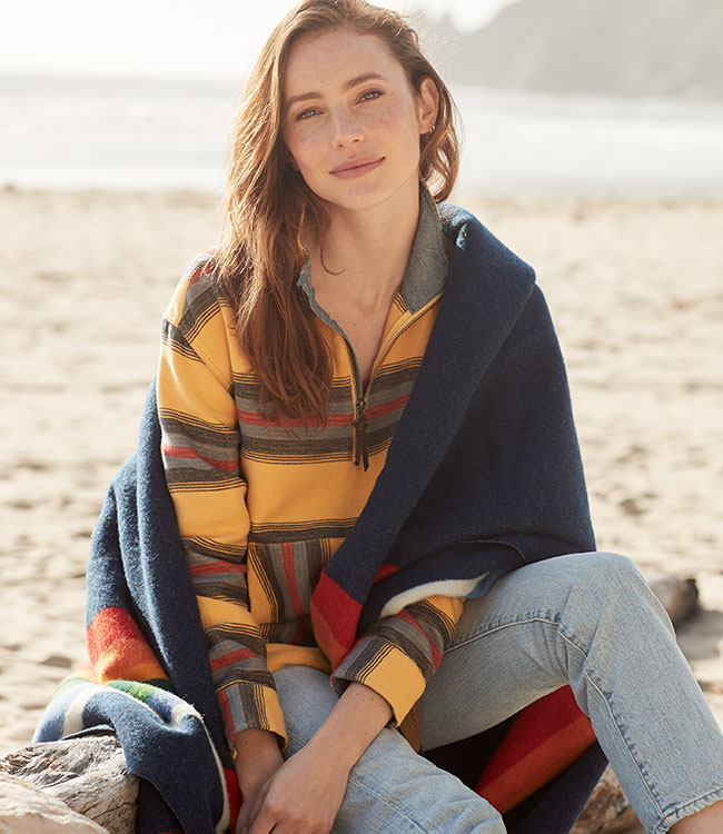 A women's model wearing the half-zip pullover in gold, wrapped in a Crater Lake blanket.