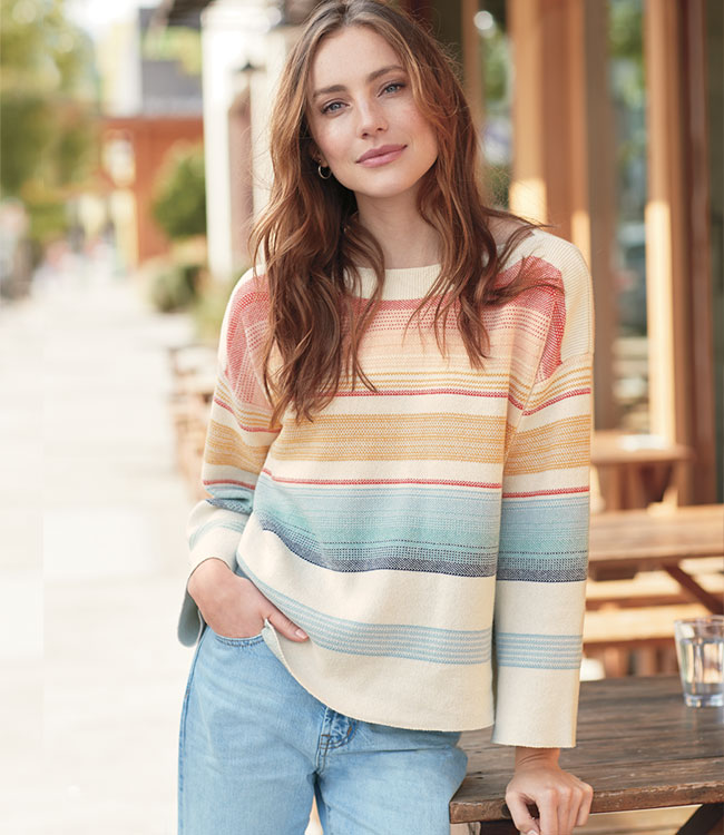 A women's model wearing a colorfully striped long-sleeve sweater