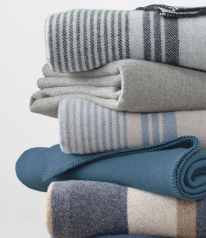 Stack of folded Eco-Wise striped and solid wool blankets