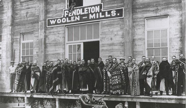 Vintage Photo of Pendleton Mill Employees Draped in Blankets Standing Outside Mill Building