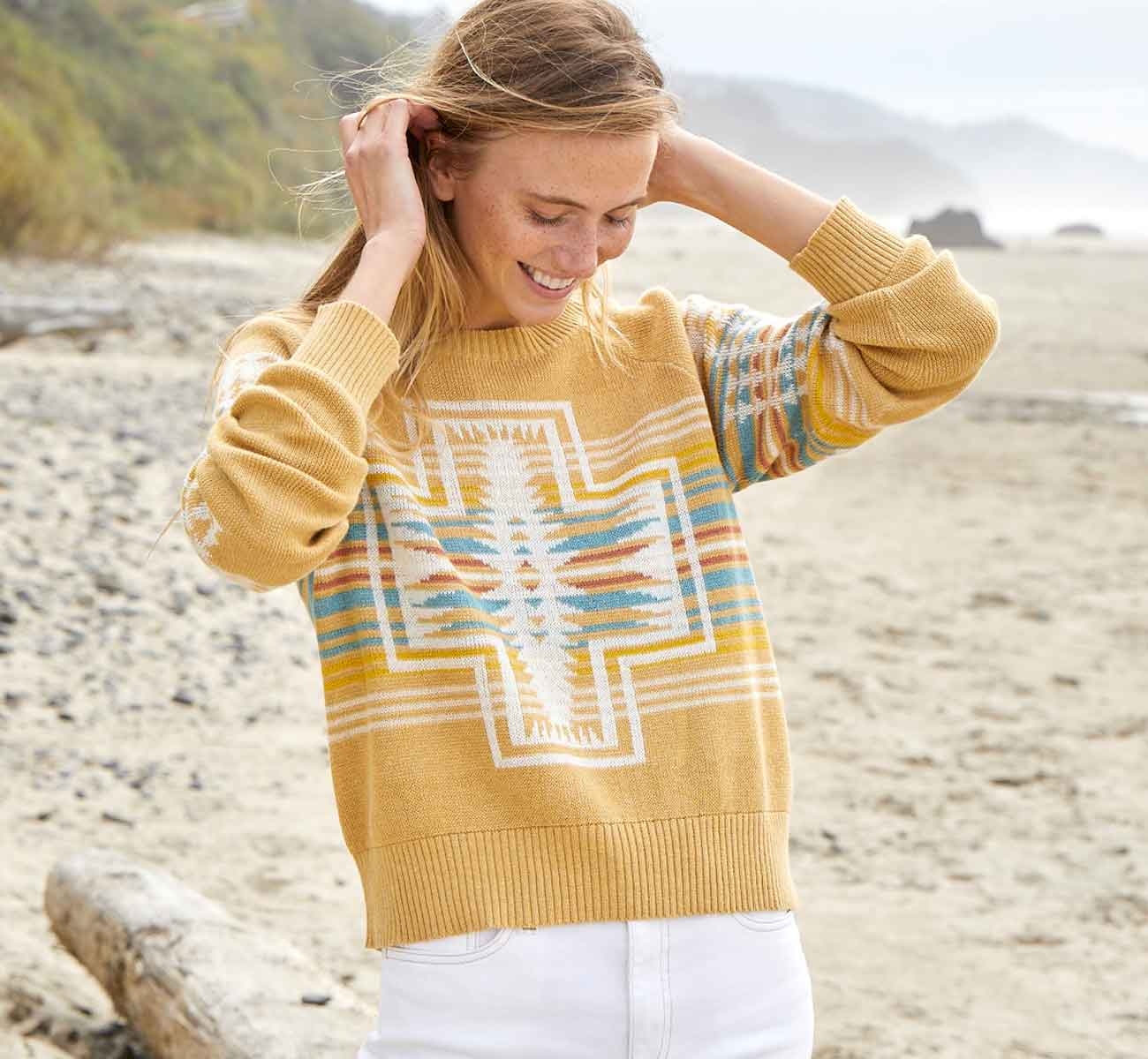 Female model in a yellow pullover sweater with a motif shown in the front