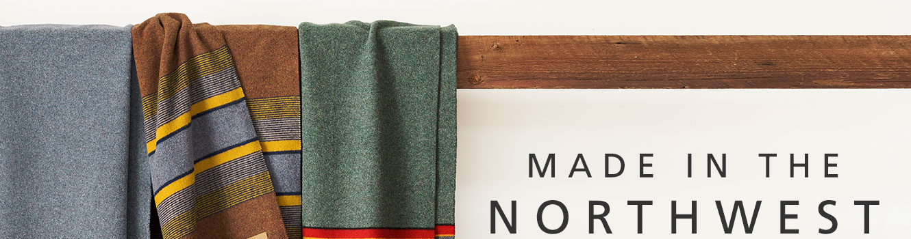 Yakima Stripe Camp Blankets Made in the Northwest hanging on a wood beam